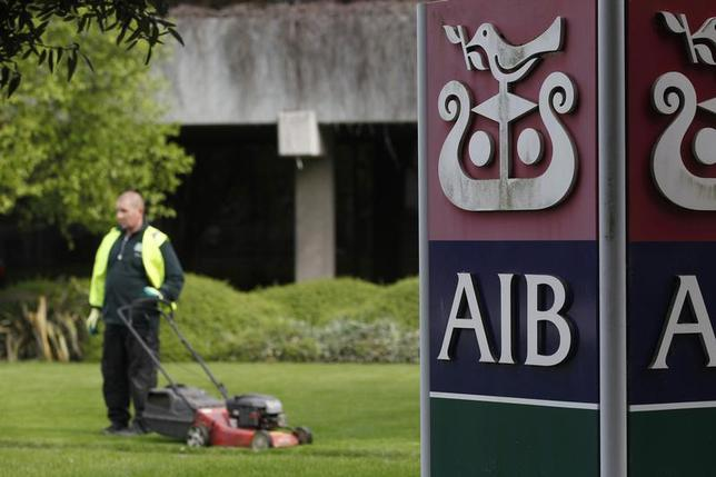 A gardener mows the grass outside the headquarters of AIB on the day the bank announced it's results, in Dublin April 12, 2011. REUTERS/Cathal McNaughton