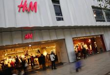 People walk past the window of an H&M textile shop in this longtime exposure photograph taken in Frankfurt December 4, 2013. REUTERS/Kai Pfaffenbach