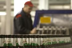 Работник на конвейере частного пивоваренного завода в Минске 19 ноября 2013 года. Президент Белоруссии Александр Лукашенко пригрозил отобрать у иностранных пивоваров местные заводы, теряющие рынок под давлением импорта из России, скакнувшего благодаря Таможенному союзу. REUTERS/Vasily Fedosenko