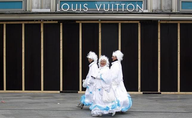 Women dressed in costumes for ''Weiberfastnacht'' (Women's Carnival) walk past a shop of Louis Vuitton in Cologne February 27, 2014. REUTERS/Ina Fassbender