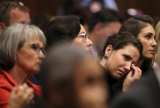 Aimee Pistorius, sister of South African Olympic and Paralympic sprinter Oscar Pistorius, reacts during her brother's trial at the North Gauteng High Court in Pretoria April 9, 2014. REUTERS-Siphiwe Sibeko-Pool