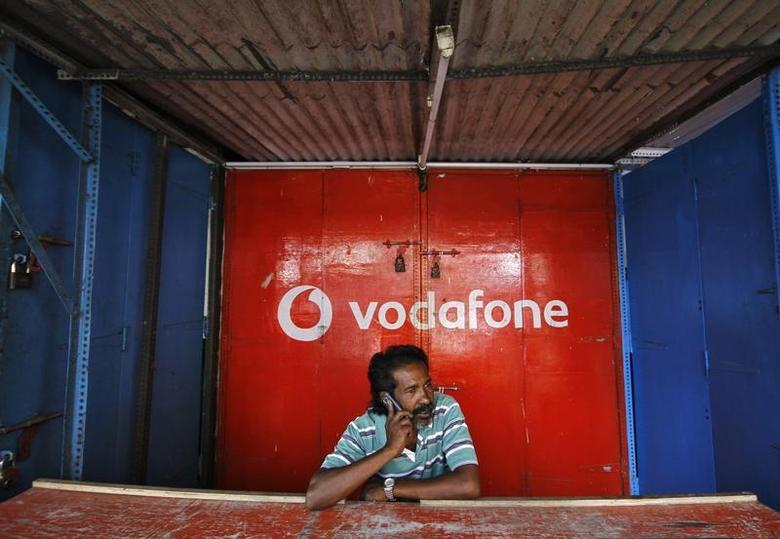 A retail shop owner speaks on his mobile phone outside his closed shop shutters painted with an advertisement for Vodafone at a market in the southern Indian city of Chennai December 30, 2013. REUTERS/Babu