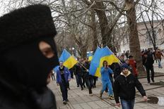 Участник сил самообороны Крыма наблюдает за маршем проукраинских активистов в Симферополе 8 марта 2014 года. Украинский прозападный активист заявил в четверг, что был похищен пророссийскими силами в Крыму и в течение 11-ти дней подвергался пыткам, прежде чем отпущен на волю в марте в обмен на другого пленного. REUTERS/Thomas Peter