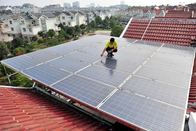 A worker examines the solar panels on the roof of a residential building in Yichang, Hubei province September 16, 2013. REUTERS/Stringer