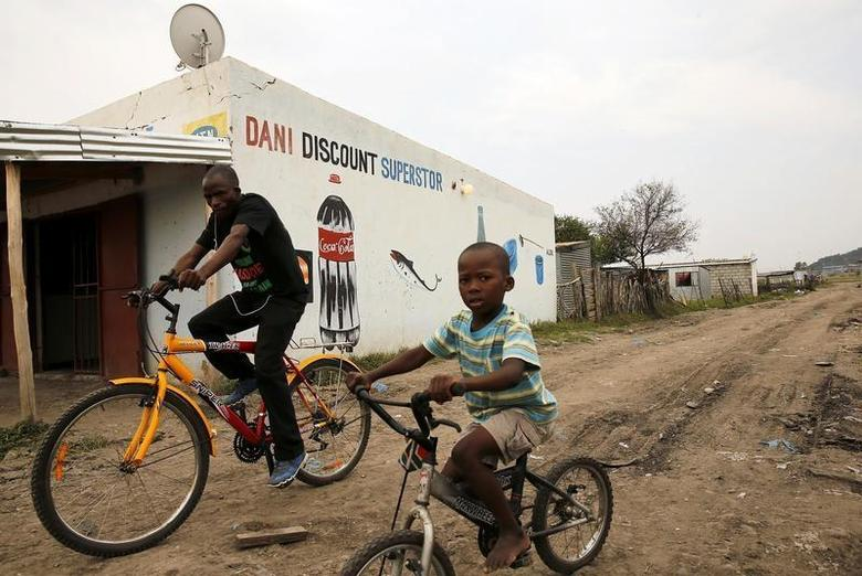 A man and his son cycle past a shop in Nkaneng, Marikana's informal settlement, in Rustenburg, April 1, 2014. REUTERS/Siphiwe Sibeko