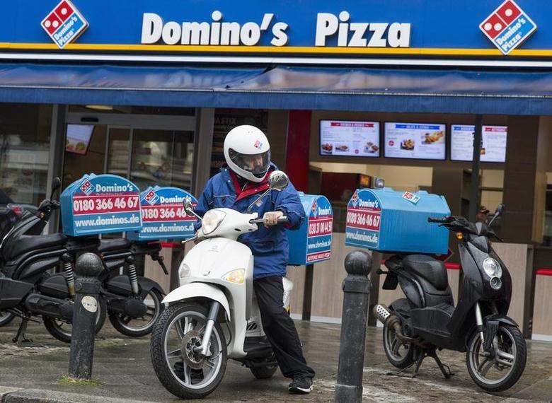 A staff member delivers take-away pizzas to customers at a Domino's Pizza store in Berlin, August 19, 2013. REUTERS/Thomas Peter