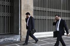 Unas personas pasan junto a la sede del Banco de Grecia en Atenas, abr 9 2014. Grecia volvió el jueves a los mercados de deuda colocando 3.000 millones de euros (4.150 millones de dólares) en bonos a 5 años con un rendimiento de 4,95 por ciento, en la parte baja de la guía inicial. REUTERS/Yorgos Karahalis