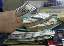 Un empleado cuenta dólares en una casa de cambios en Manila, sep 19 2013. El Gobierno de Estados Unidos registró un déficit de presupuesto de 37.000 millones de dólares en marzo, frente a la brecha de 107.000 millones de dólares del mismo mes del año pasado, dijo el jueves el Departamento del Tesoro. REUTERS/Romeo Ranoco