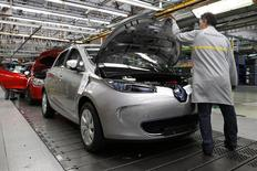An employee works on a Renault Zoe electric car on the production line at the Renault automobile factory in Flins, west of Paris, May 28, 2013. REUTERS/Benoit Tessier