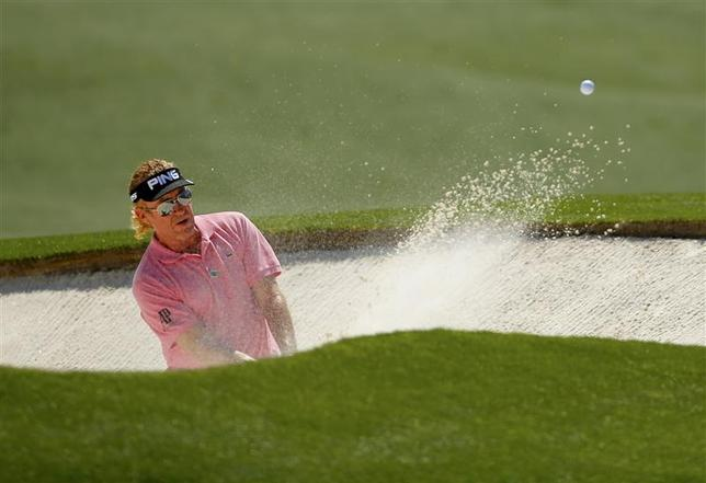 Spain's Miguel Angel Jimenez hits from the sand on the 18th hole during the first round of the 2014 Masters golf tournament at the Augusta National Golf Club in Augusta, Georgia April 10, 2014. REUTERS/Brian Snyder