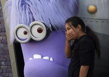 "A girl laughs while standing with a purple Evil Minion character at the new ""Despicable Me Minion Mayhem"" ride during technical rehearsals for the new attraction at Universal Studios Hollywood in Universal City, California March 28, 2014. REUTERS/Jonathan Alcorn"