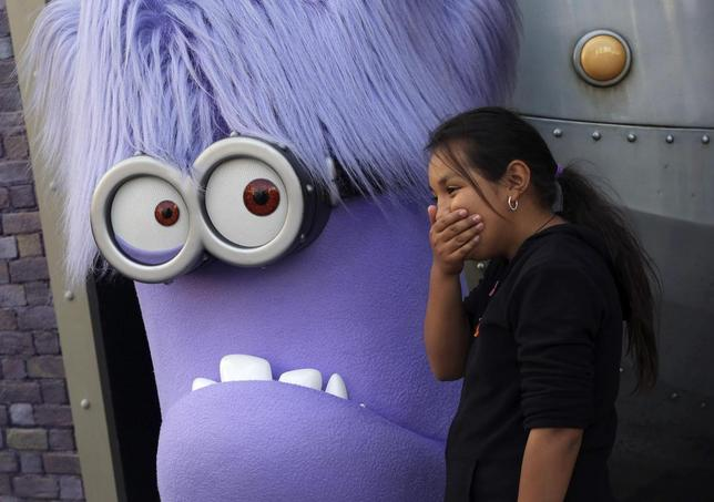 A girl laughs while standing with a purple Evil Minion character at the new ''Despicable Me Minion Mayhem'' ride during technical rehearsals for the new attraction at Universal Studios Hollywood in Universal City, California March 28, 2014. REUTERS/Jonathan Alcorn