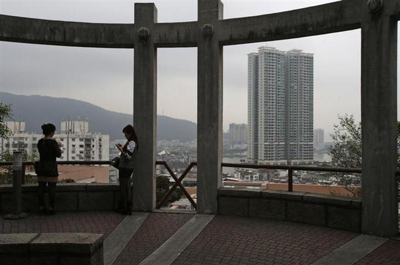 People rest at a park overlooking the Macau peninsula March 17, 2014. REUTERS/Bobby Yip/Files