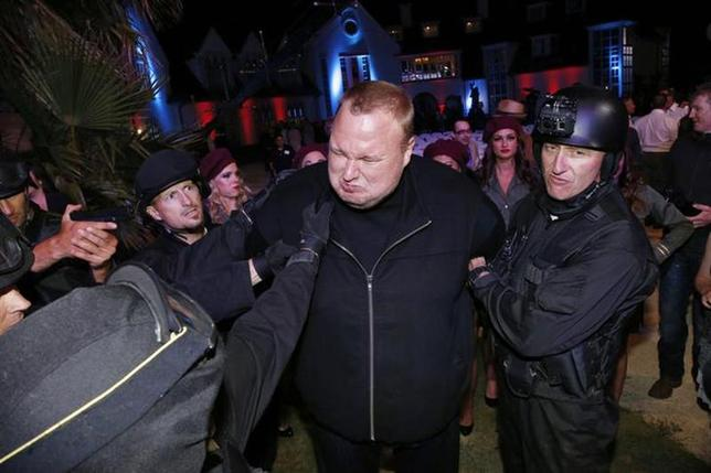 Actors in police costume mock-arrest Megaupload founder Kim Dotcom (C), as he launches his new file sharing site ''Mega'' in Auckland January 20, 2013. REUTERS/Nigel Marple/Files
