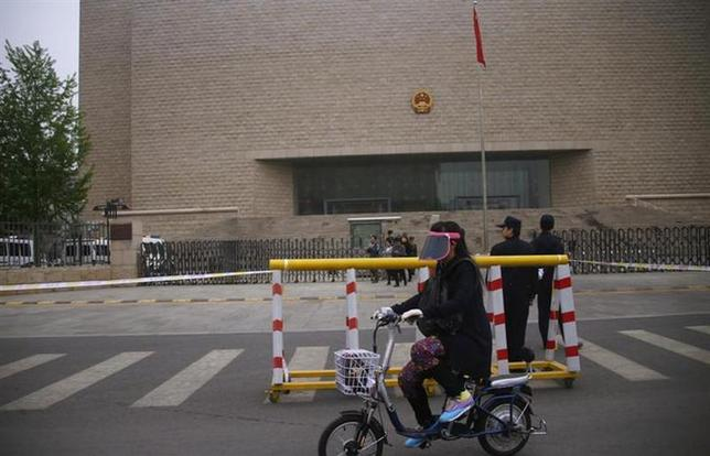 A woman cycles past a police barricade outside an entrance to Beijing Municipal High People's Court during a verdict appeal hearing for Chinese rights activist Xu Zhiyong, in Beijing, April 11, 2014. REUTERS/Petar Kujundzic