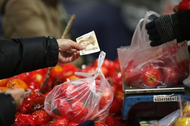 A customer pays money after purchasing tomatoes at a market in Beijing February 14, 2014. REUTERS/Kim Kyung-Hoon