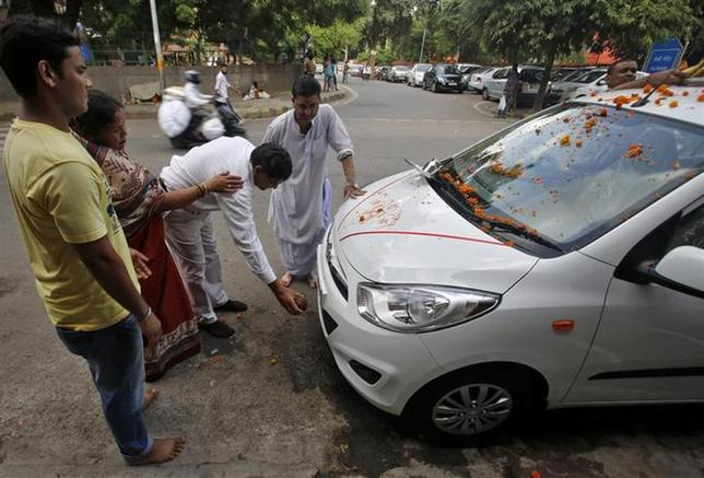 A Hindu priest (2nd R) blesses a new car with its owners outside a temple in New Delhi September 2, 2013. REUTERS/Anindito Mukherjee/Files