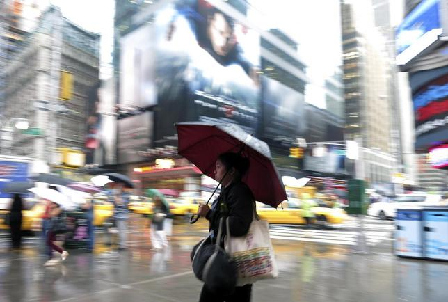 A woman walks through Time Square during a rain storm in New York June 3, 2013. REUTERS/Gary Hershorn