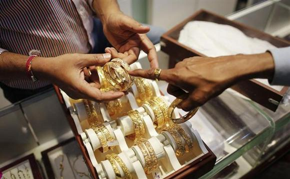 An employee shows gold bangles to a customer at a jewellery showroom on the occasion of Dhanteras at a market in Mumbai November 1, 2013. REUTERS/Danish Siddiqui/Files