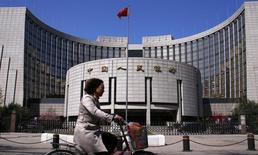 """Женщина проезжает мимо здания Народного банка Китая в Пекине 3 апреля 2014 года. Китайское правительство и центробанк должны быть """"очень осторожны"""" при осуществлении любых программ стимулов, поскольку они обычно менее эффективны, нежели естественные рыночные силы, сказал представитель Народного банка Китая. REUTERS/Petar Kujundzic"""