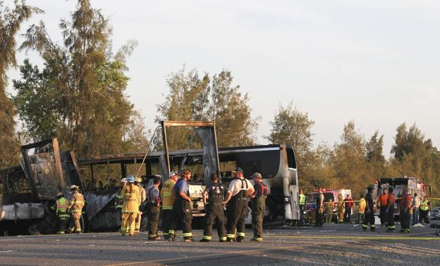 Rescue workers, police and firefighters survey the scene where a truck and a tour bus collided on Interstate 5 near Highway 32 near Orland, California, April 10, 2014. MANDATORY CREDIT REUTERS-Greg Barnette-Record Searchlight
