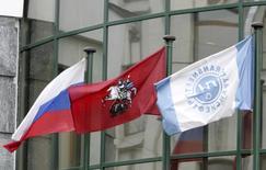 Флаги РФ, Москвы и Транснефти у центрального офиса компании в Москве 9 января 2007 года. Российская трубопроводная монополия Транснефть сократила чистую прибыль по МСФО на 15 процентов в 2013 году, но обещает повысить вознаграждение акционеров, главным из которых выступает государство. REUTERS/Anton Denisov