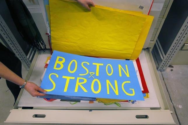 Archivist Marta Crilly holds a poster, an artifact saved from the makeshift Boston Marathon bombing memorial, at the City Archives in Boston, Massachusetts March 27, 2014. REUTERS/Brian Snyder