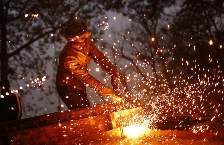 A worker uses a welding torch to weld an iron machine at the construction site of a flyover in New Delhi January 6, 2014. REUTERS/Anindito Mukherjee/Files
