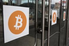 Unas pegatinas alusivas a bitcoin en unas puertas durante la conferencia Inside Bitcoins: The Future of Virtual Currency en Nueva York, abr 8 2014. Dos de los más grandes operadores en China de bitcoin dijeron que algunos bancos del país cerrarían sus cuentas la semana que viene, en el más reciente revés para la moneda virtual. REUTERS/Lucas Jackson