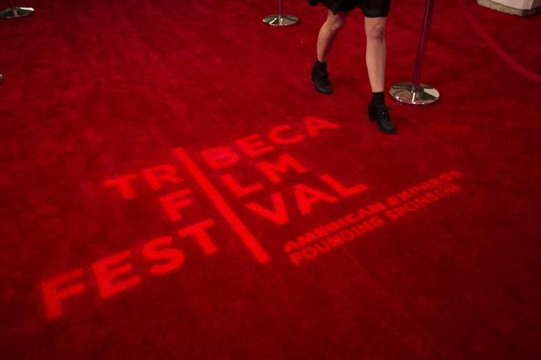 A woman walks past a logo displayed on a red carpet on the opening night of the Tribeca Film Festival in New York, April 17, 2013. REUTERS/Lucas Jackson