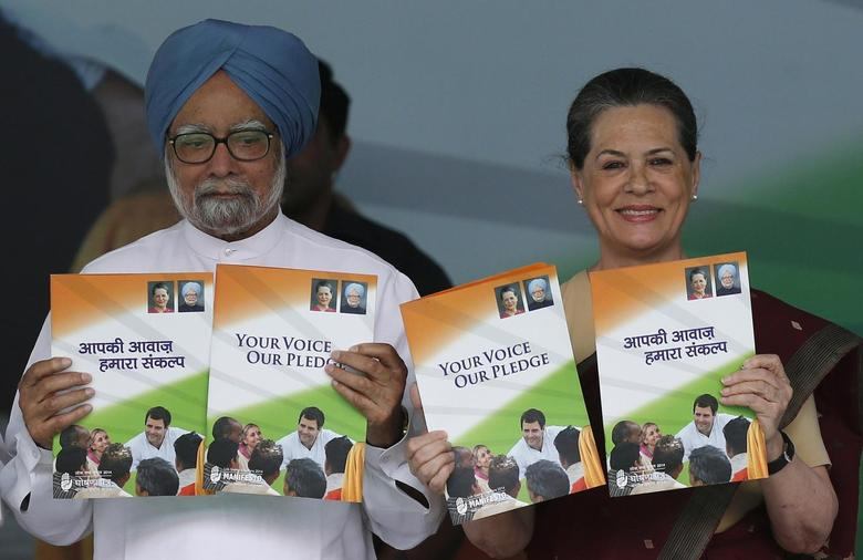 India's Prime Minister Manmohan Singh (L) and Chief of India's ruling Congress party Sonia Gandhi hold their party's manifesto for the April/May general election in New Delhi March 26, 2014. REUTERS/Adnan Abidi