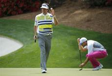 U.S. golfer Bubba Watson waves after making a birdie on the 13th hole as Spain's Sergio Garcia places his ball during the second round of the Masters golf tournament at the Augusta National Golf Club in Augusta, Georgia April 11, 2014. REUTERS/Mike Blake