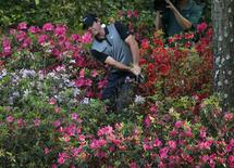 Northern Ireland's Rory McIlroy hits from the azaleas on the 13th hole during the second round of the Masters golf tournament at the Augusta National Golf Club in Augusta, Georgia April 11, 2014. REUTERS/Mike Blake