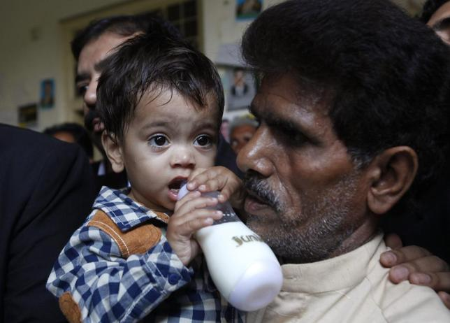 Nine-month-old baby Musa Khan drinks milk from his bottle while being carried by his grandfather Muhammad Yasin as they leave after appearing in a court in Lahore April 12, 2014. REUTERS/Mohsin Raza