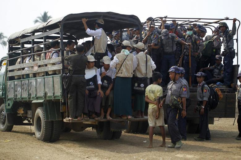 Volunteers and police board vehicles before proceeding to Rohingya refugee camps to collect data for the census in Sittwe March 31, 2014. REUTERS/Soe Zeya Tun