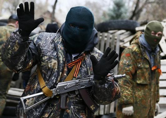 An armed man gestures in front of the police headquarters in Slaviansk, April 12, 2014. REUTERS-Gleb Garanich