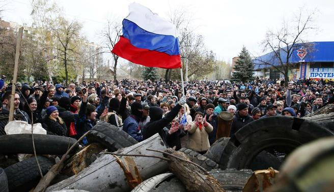 Pro-Russian protestors wave the Russian flag in front of the police headquarters in Slaviansk, April 12, 2014. REUTERS-Gleb Garanich