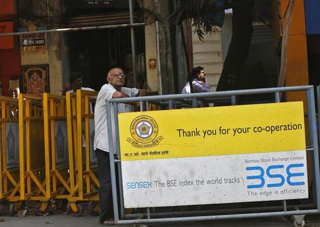 A man looks at a screen across the road displaying the Sensex on the facade of the Bombay Stock Exchange (BSE) building in Mumbai February 6, 2014. REUTERS/Mansi Thapliyal/Files