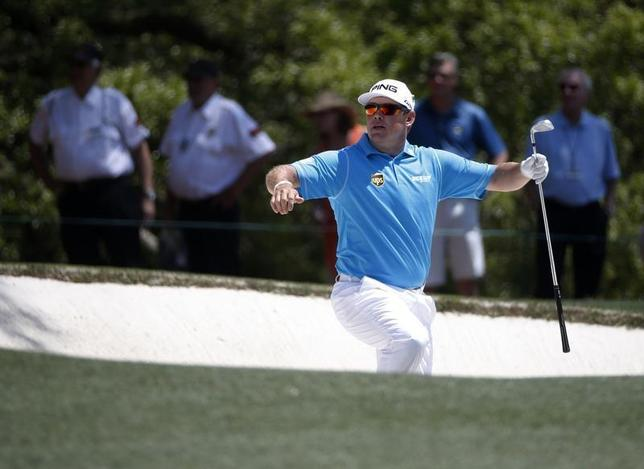 Britain's Lee Westwood climbs from the sand trap after a shot on the first hole during the third round of the Masters golf tournament at the Augusta National Golf Club in Augusta, Georgia April 12, 2014. REUTERS/Mike Segar