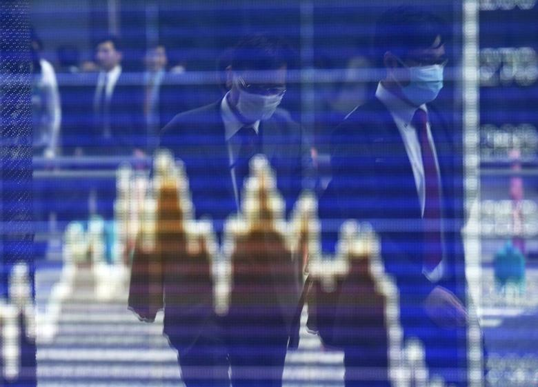 Men, wearing masks, are reflected on a screen displaying a graph showing movements of Shanghai B shares outside a brokerage in Tokyo April 9, 2014. REUTERS/Issei Kato