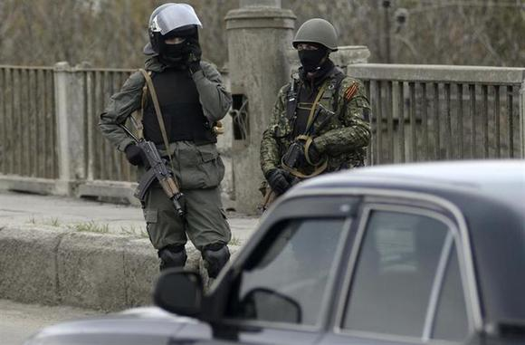 Armed men stand at an improvised checkpoint in Slaviansk, April 12, 2014. REUTERS/Maks Levin