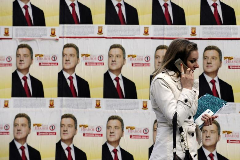 A woman walks past campaign posters of Macedonian ruling party VMRO-DPMNE presidential candidate and current President of Macedonia Gjorge Ivanov in Skopje April 11, 2014. REUTERS/Ognen Teofilovski