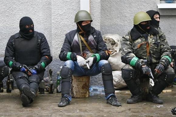 Pro-Russian armed men sit near the police headquarters in Slaviansk April 13, 2014. Ukraine's Interior Minister on Sunday told residents in the eastern city of Slaviansk to stay indoors, in anticipation of clashes between pro-Russian militants who have seized official buildings and Ukrainian security forces. REUTERS/Gleb Garanich