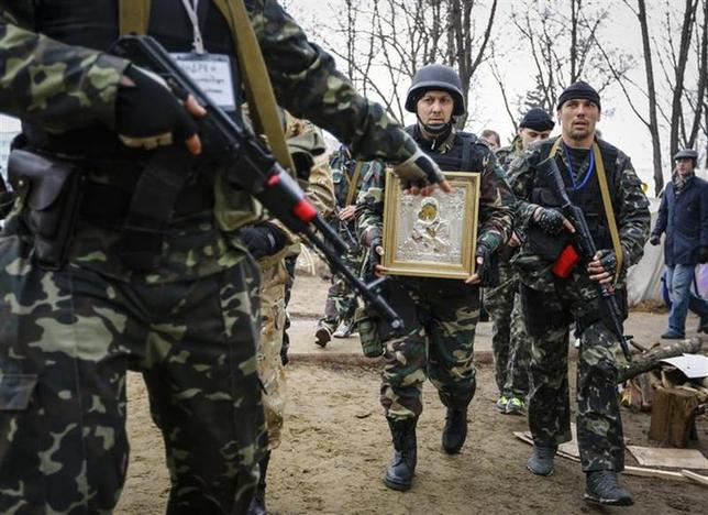 Armed pro-Russian protesters escort a comrade who is carrying an icon, which they said was found in the seized office of the SBU state security service, in Luhansk, in eastern Ukraine April 13, 2014. REUTERS/Shamil Zhumatov
