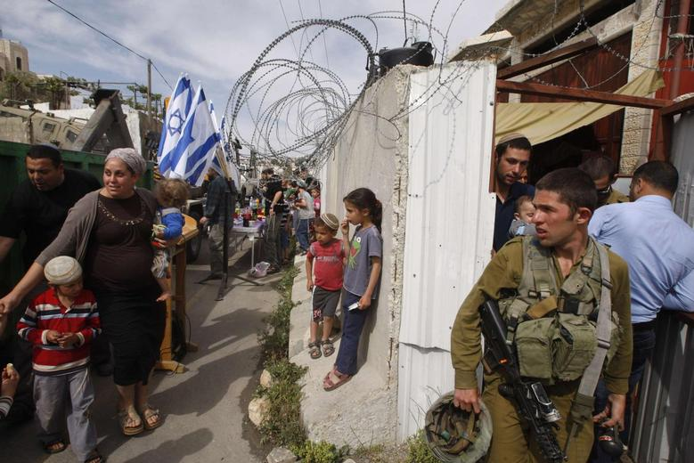 An Israeli soldier stand guard as settlers move into a house disputed over by Israeli settlers and Palestinians in the West Bank city of Hebron April 13, 2014. REUTERS/ Mussa Qawasma
