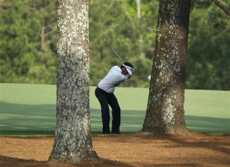 U.S. golfer Bubba Watson hits a shot from behind the trees on the 15th hole during the final round of the Masters golf tournament at the Augusta National Golf Club in Augusta, Georgia April 13, 2014. REUTERS/Mike Blake