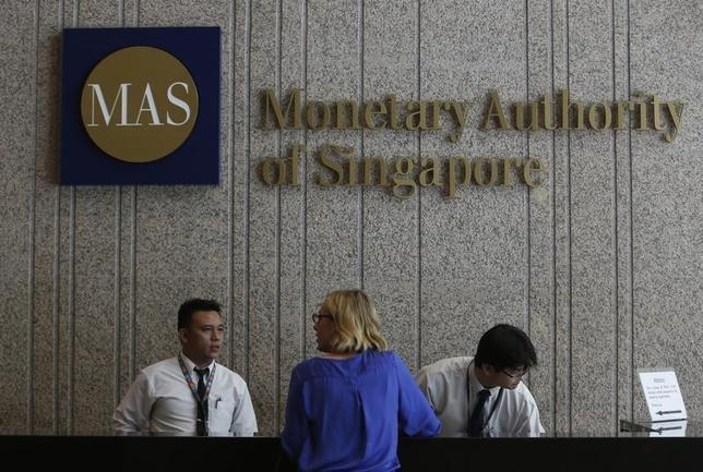 A visitor speaks to security officers at the building of the Monetary Authority of Singapore (MAS) in Singapore February 21, 2013. REUTERS/Edgar Su