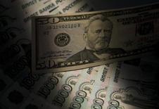 Купюры валют доллар США и рубль в Москве 17 февраля 2014 года. Рубль упал к трехнедельным минимумам при открытии биржевых торгов понедельника из-за угрозы военных действий на юго-востоке Украины, опасений возможности прямого вмешательства России в конфликт, вероятности новых западных санкций. REUTERS/Maxim Shemetov