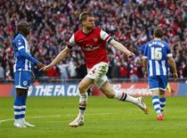 Arsenal's Per Mertesacker celebrates his goal against Wigan Athletic during their English FA Cup semi-final soccer match at Wembley Stadium in London April 12, 2014. REUTERS/Eddie Keogh