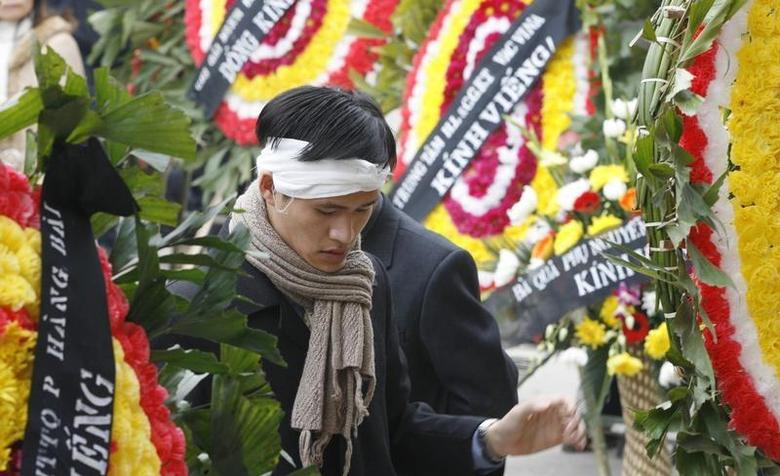 Vietnamese dissident Nguyen Tien Trung stands between wreaths during a funeral for Hoang Minh Chinh in Hanoi February 16, 2008. REUTERS/Kham
